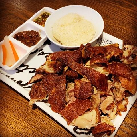 German crispy pork leg marinated with Thai herbs, served with tamarind chilli paste, Jaew sauce & sticky rice.
